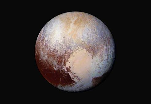 Four images from New Horizons' Long Range Reconnaissance Imager were combined with color data from the Ralph instrument to create this enhanced color global view of Pluto. Credit: NASA/JHUAPL/SwRI